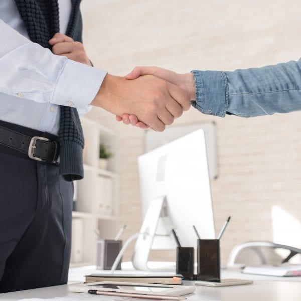 Imagem ilustra dois homens fechando negócio
